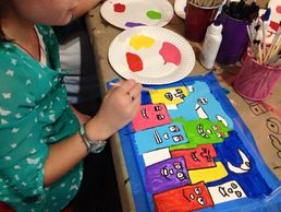 Student's working on a James Rizzi painting from the Color Wheel Art Curriculum.