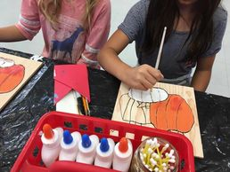 Second graders painting pumpkins on wood inspired by Paul Cezanne.