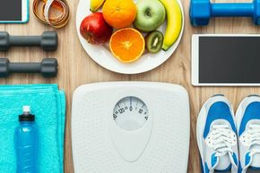 weight scale running shoes waterbottle weights fruit on a white plate diet