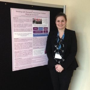 A trustee standing in front of a poster presentation at a conference
