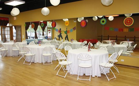 Studio space with tables and chairs available for birthday parties, graduations, baby showers