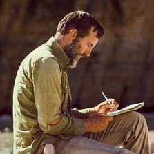Edward Paul Abbey writes on a notepad in front of a cliff face.