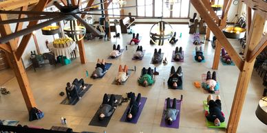 People on yoga mats in a large, timber frame room. Light fixture made out of wine barrel hoops.