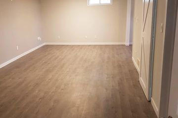 New flooring in a basement renovation completed by Edmonton Paint Professionals/Cobra Contracting.