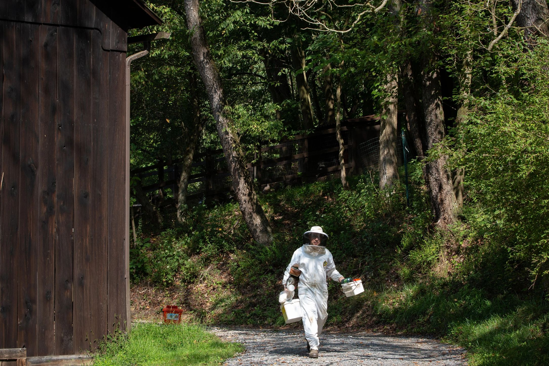 Joe Zgurzynski carries beekeeping equipment down the gravel path next to the barn.