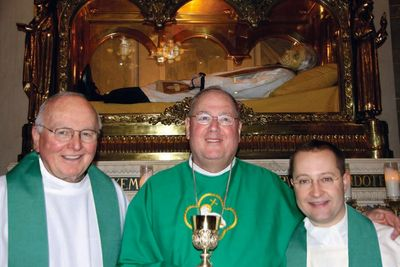 Msgr. Shea, Cardinal Dolan, Fr. Marcello, at the tomb of St. John Vianney in Ars, France.