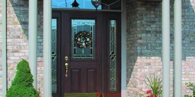 Wood Entry Door with glass inlay, round gray columns brick home