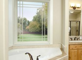 picture window with cross etching above bathtub