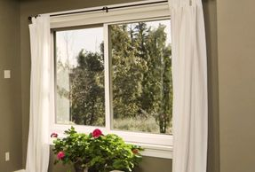 horizontal slider window with white curtains and pink roses
