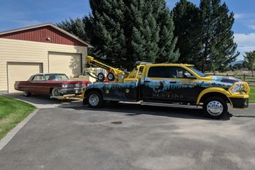 tow truck with classic car attached sits in driveway
