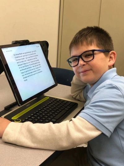 This image is of a boy wearing a blue shirt and glasses  sitting at a desk using the Patriot Pro
