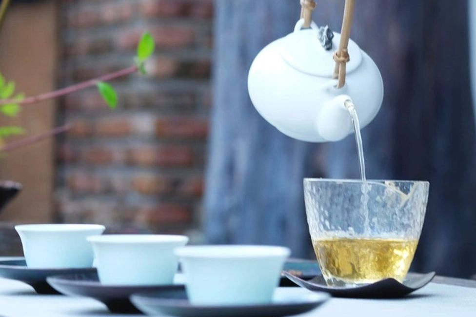 white tea kettle pouring green tea  into clear mug.