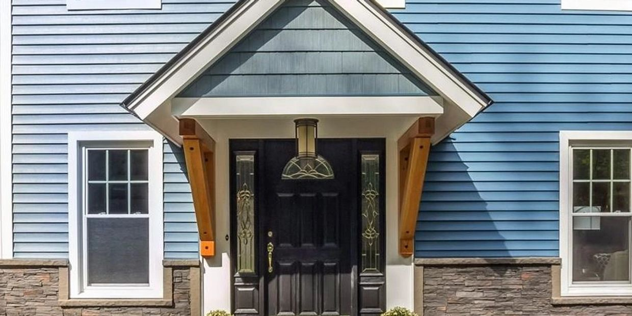 Craftsman style porch roof with timber frame support brackets. Faux stone siding.