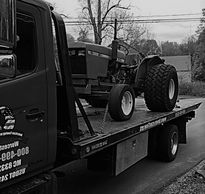 Farm tractor and construction equipment being towed and transported in Worcester, MA by American Tow