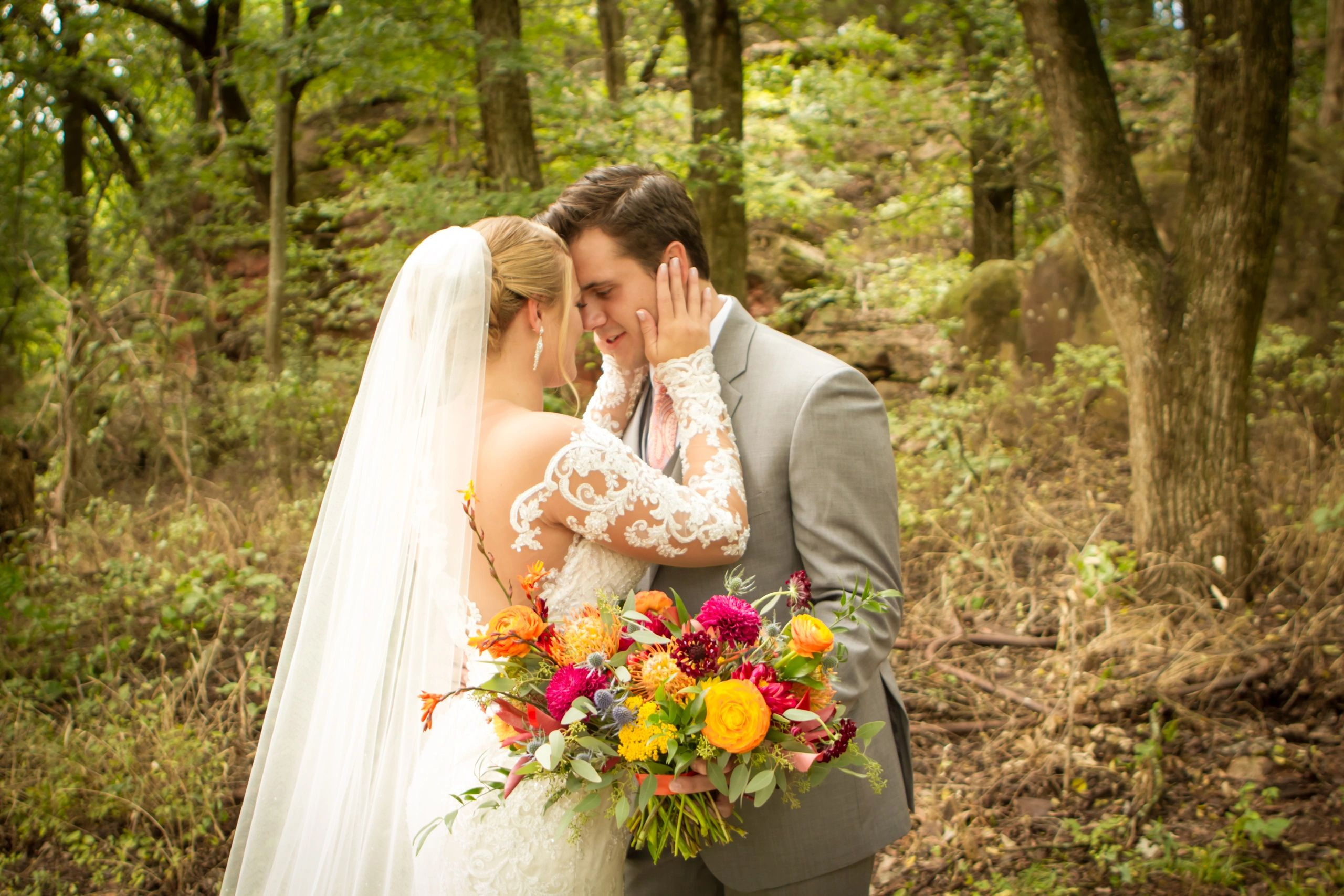 Wedding photo of bride and groom in the woods embracing one another.