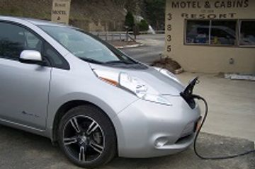 Electric Car Charger attached to car with waterfall in the background
