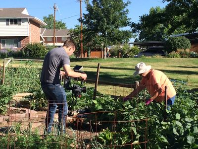 "A HaveyPro cameraman films in Cherry Creek 3's Community Garden for ""Doing More with Less"" (2017)."
