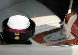 Cup holder in a car with a insert holding a cup of coffee securely. The KAZeKUP® Ultimate Cup Holder insert catches spills and drips.