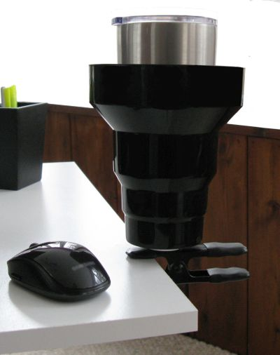 Cup Holder clipped on desk. Clip on Cup Holder holds drinks securely and out of the way. Clip the KAZeKUP Cup Holder in your work station, studio, shop and more