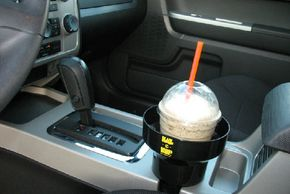 Drink being held securely in a auto cup holder insert. Any drips, spills or condensation are captured and stored in the base of the KAZeKUP®.