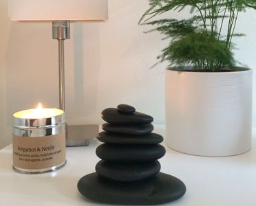 Smooth basalt stones balanced in a pillar, used in hot stones reflexology therapy