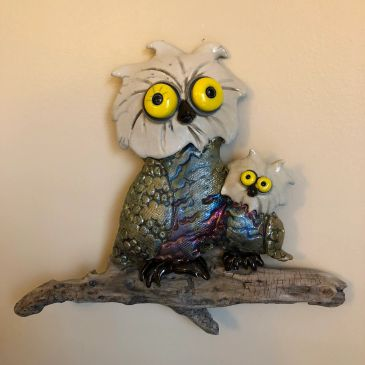 Big owl and small owl cuddling on a branch