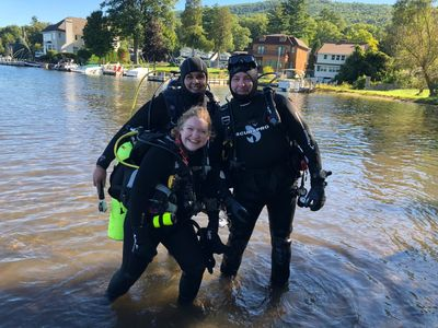 scuba divers standing in lake