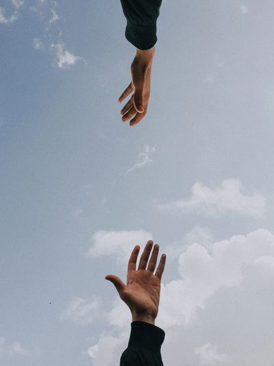 2 arms reaching  to each other to clasp hands w/sky background.   Unsplash image by Youssef Naddam.