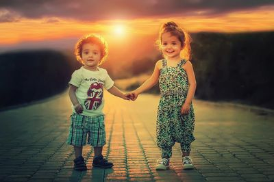 2 Kids holding hands with the Sun in the background.