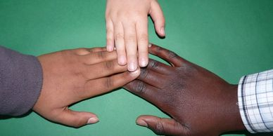 The hands of three adolescents of three different races reaching for each other