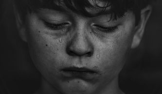 A dark image of a young child weeping; tears run down their cheek.