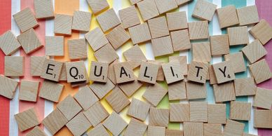 "Several Scrabble tiles lay face down on a surface with rainbow and white stripes. The tiles facing upward spell out the word ""Equality."""
