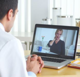 A physician listens to a patient who is speaking with them remotely via a web application