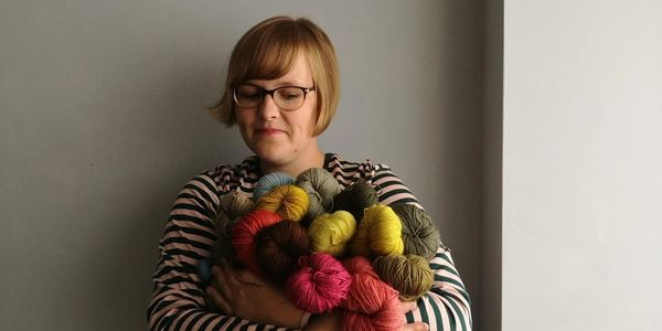 Woman holding hand dyed yarn in her arms