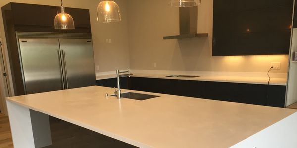 "Livingstone solid surface ""Brisk"" paired with dark cabinetry adds that clean crisp modern look."