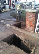 AVS hydrovac excavation dug under a concrete curb to make a trench for underground power