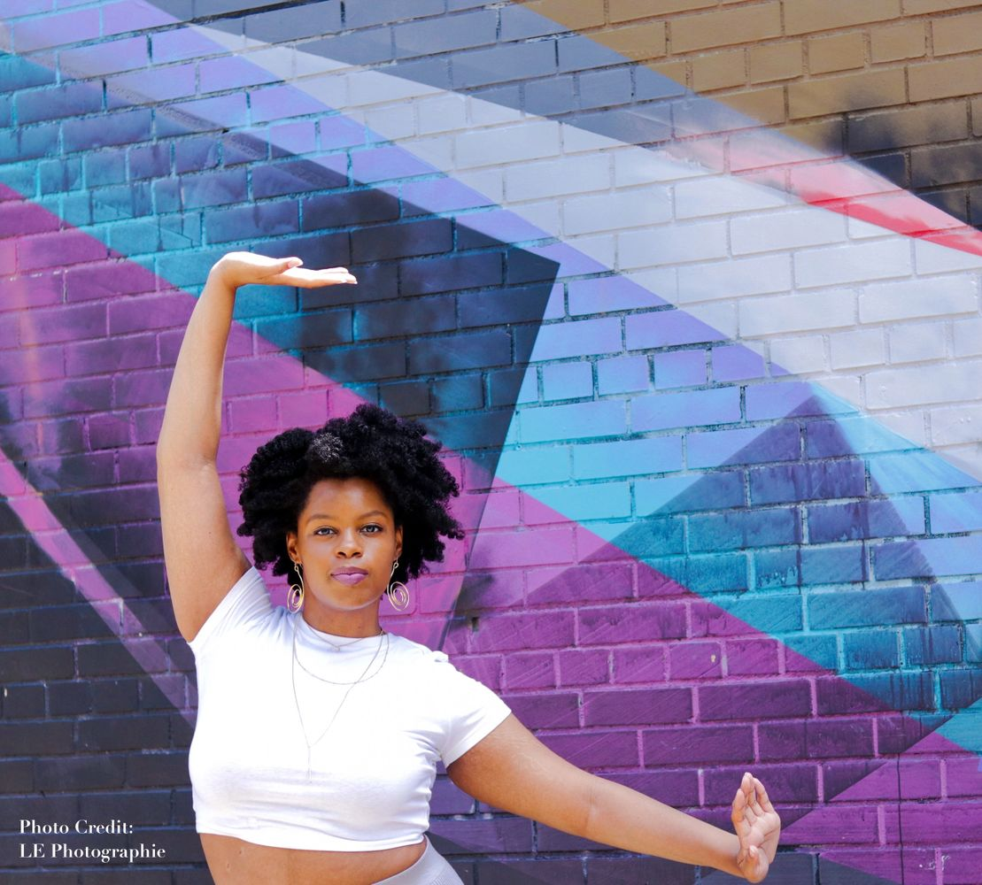Black woman wearing a white shirt and curly afro, with arms out in front of a blue and purple mural