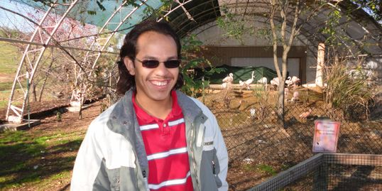 Man wearing red and white striped shirt and sun glasses smiling in front of a flamingo area.
