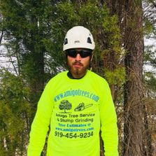 Bearded man wearing safety goggles, white helmet, and yellow shirt standing in front of evergreens.