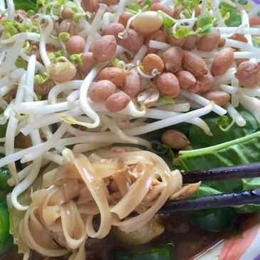 PHO, bone broth with rice noodles, fresh greens, bean sprouts, fresh peanut are dropped on top.