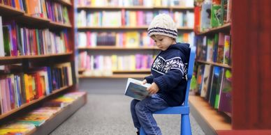 Child reading a book independently in the library.