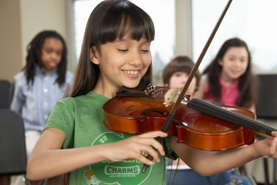 Smiling girl playing the violin with other kids behind her