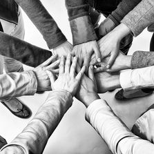 A black and white image of hands coming together to form a group huddle