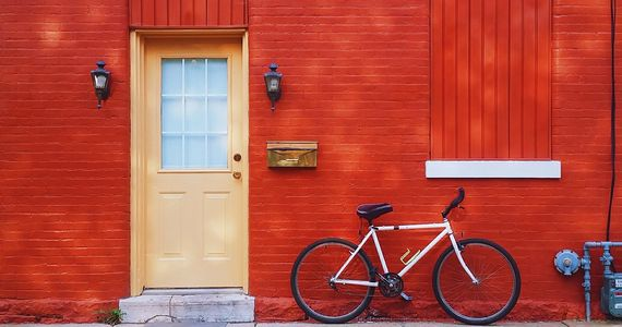 White bicycle leans against brick wall painted red, next to a pale yellow door.