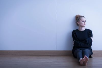 Young woman sitting on the floor against a white wall looking distressed.