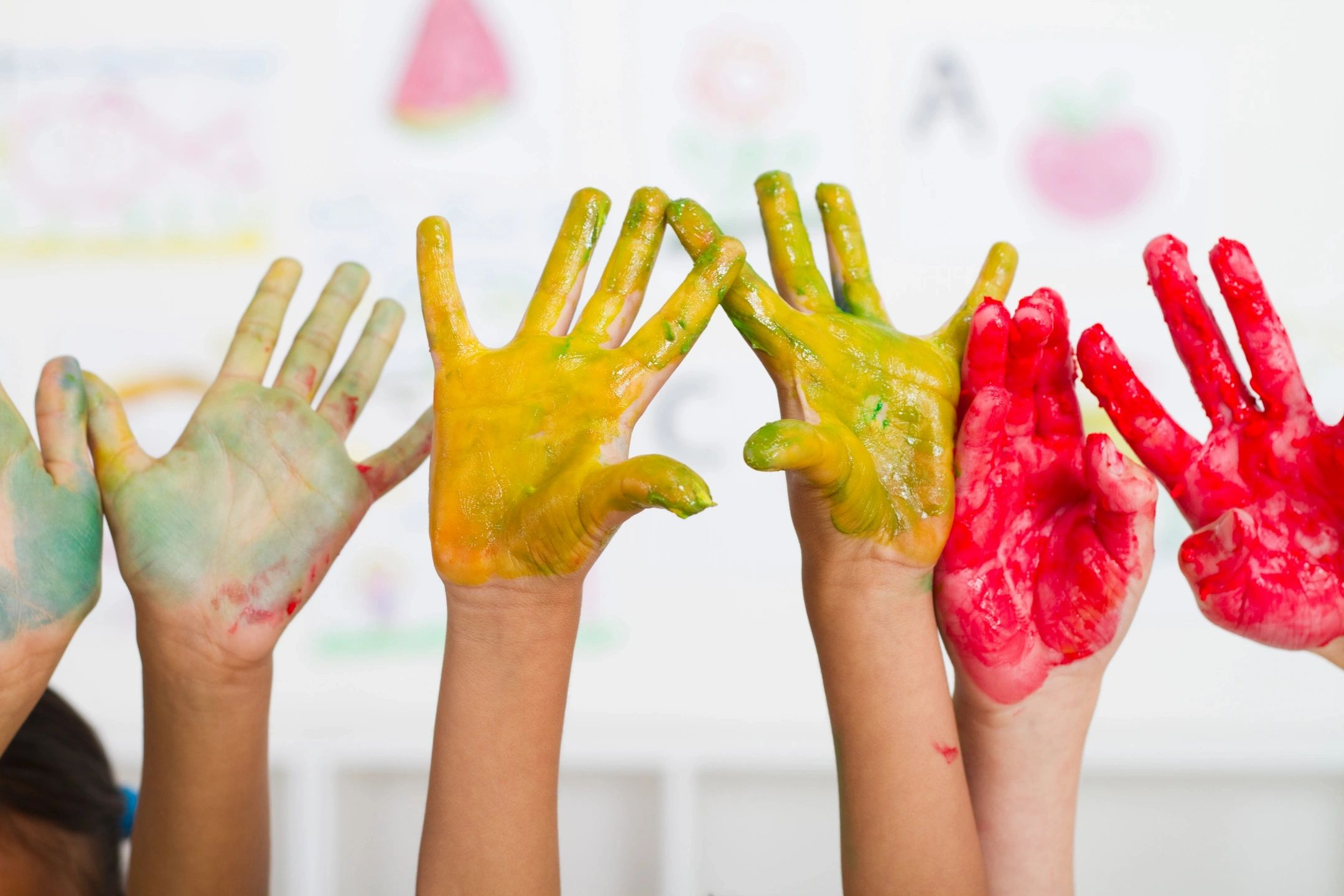 Small hands covered in bright paint held high in the air for the camera