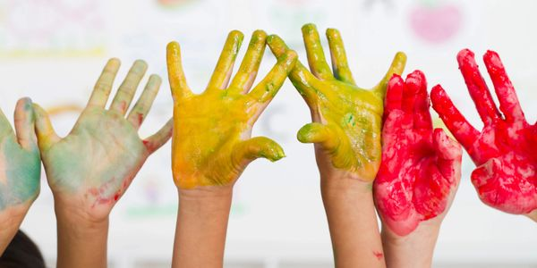 Children's raised paint-covered hands