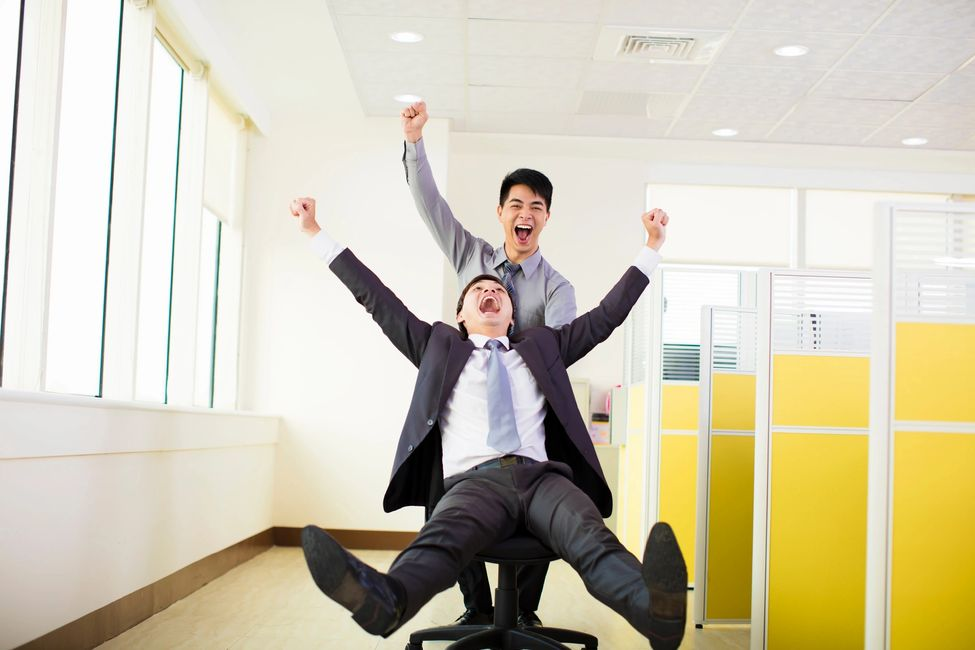 Man pushing a coworker in an office chair on wheels past cubicles laughing with arms raised.