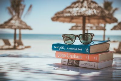 Three books on a table with a pair of sunglasses with tropical huts and a Caribbean ocean view in the background.