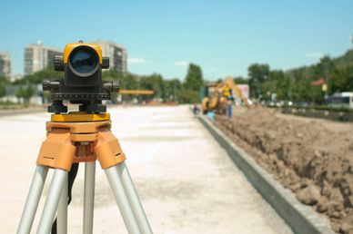 Theodolite outdoors on new road and a bright day.